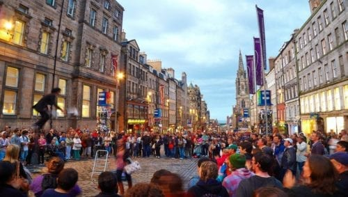 A crowd watches a performer at the Edinburgh Fringe Festival in the evening