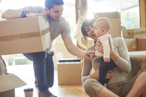 Couple with a baby moving house with movers