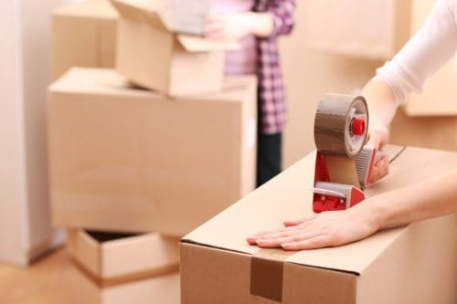 Using packing tape to close a box before moving day