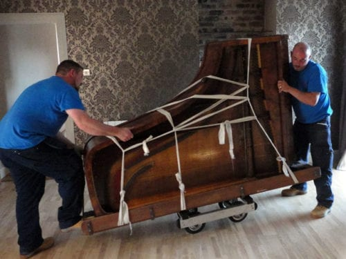 Movers transporting a grand piano