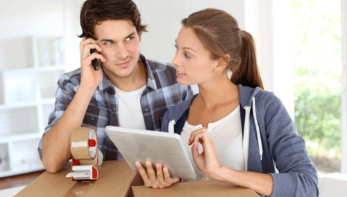 Couple looking at removal costs by comparing quotes on a tablet