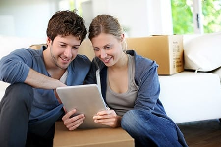 A couple using a tablet to compare prices for a house removal