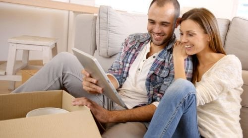 A couple researching about hiring a furniture removal on their tablet