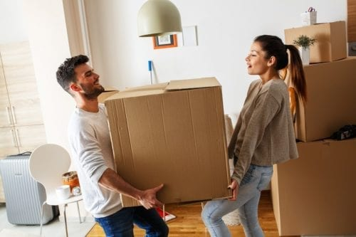 Young couple carrying a large box at their new house. Removals Manchester.