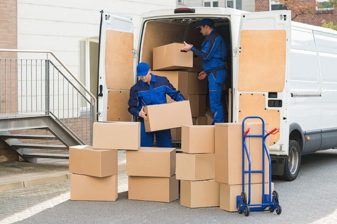 Movers loading boxes onto a removal van