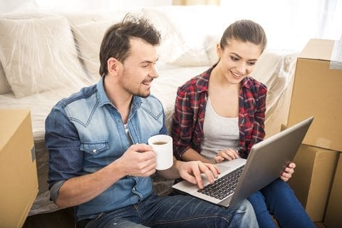 Couple looking for London removal companies on their laptop