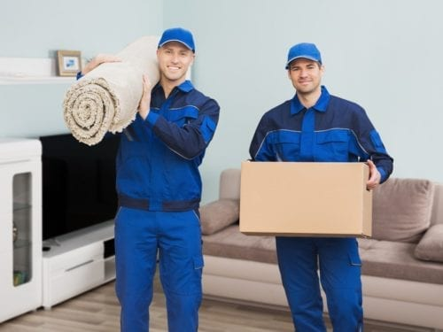 Movers carrying a rug and a box. Professional removal services.