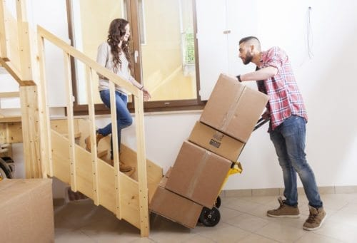Young couple carrying moving boxes into their new house