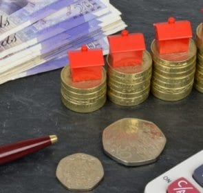 Coins, paper money, and calculator to signify the cost of moving house